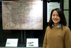 Photo Sakoto Nakamoto in front of library display and map. Photo credit Wes Adams/CTSI