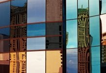 alt= glass building with reflection of other buildings